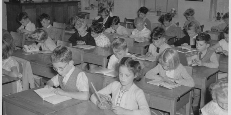 1950s schoolchildren sitting at desks 777x388